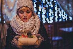 Woman with christmas present in hands near christmas lights Royalty Free Stock Photo