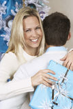 Woman With Christmas Present Hugging Man Royalty Free Stock Images