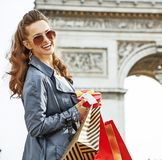Woman with Christmas present near Arc de Triomphe in Paris. Stylish Christmas in Paris. Portrait of happy young woman in sunglasses with shopping bags and Royalty Free Stock Images