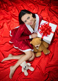 Woman with Christmas present on red background Royalty Free Stock Images