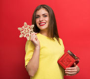 Woman with Christmas present and a snowflake Stock Photos
