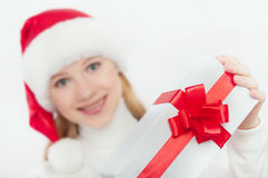 Woman and Christmas present, white gift with a red ribbon Royalty Free Stock Photography
