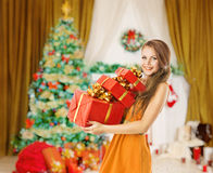Woman Christmas Presents Gifts Boxes, Holiday Model Girl. Woman Hold Christmas Presents Gifts Boxes, Model Girl in Holiday Room with Xmas Tree Royalty Free Stock Photography