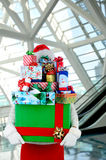 Woman with Christmas Presents in Mall. Woman carrying a large stack of christmas presents in a modern shopping mall. Woman is hidden behind the presents stock images