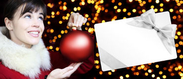 Woman with christmas red ball and gift card in golden lights Royalty Free Stock Photography