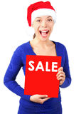 Woman with christmas sale sign. Excited christmas woman with santa hat holding red sale sign. Isolated on white background Royalty Free Stock Photography
