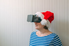 Woman with Christmas Santa Claus hat and VR headset Royalty Free Stock Photography
