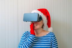 Woman with Christmas Santa Claus hat and VR headset Royalty Free Stock Images