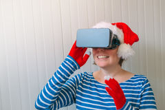 Woman with Christmas Santa Claus hat and VR headset Stock Photos