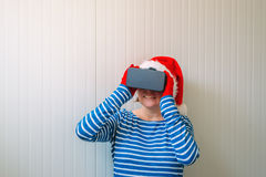 Woman with Christmas Santa Claus hat and VR headset Stock Images
