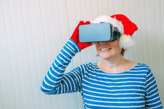 Woman with Christmas Santa Claus hat and VR headset Stock Photography