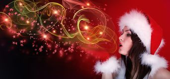 Woman in Christmas santa hat blowing flying magic glow star. Woman in Christmas santa hat blowing flying magic glow star on red snow flame dream new year Royalty Free Stock Image