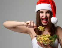 Woman in Christmas santa hat happy screaming eating Olivier salad. On grey background Royalty Free Stock Photography