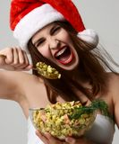 Woman in Christmas santa hat happy screaming eating Olivier salad. On grey background Royalty Free Stock Images