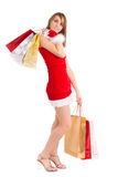 Woman christmas shopping. Happy young woman in santa suit carrying shopping bags Stock Photos