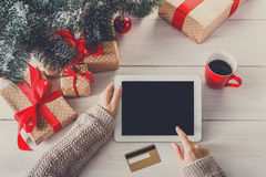 Woman christmas shopping online with a credit card. Christmas online shopping above view on wood. Female buyer touch screen of tablet, copy space. Woman has stock photography
