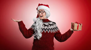 Woman in Christmas sweater and Santa hat with presents Royalty Free Stock Photos
