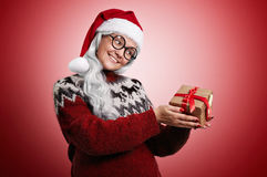 Woman in Christmas sweater and Santa hat with presents stock images