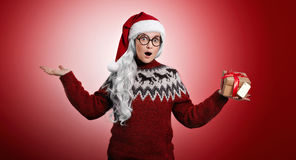 Woman in Christmas sweater and Santa hat with presents. Surprised woman with long white hair and round glasses in Santa`s hat and red Christmas sweater with a royalty free stock photography