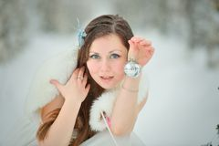 Woman with Christmas toys in winter forest Royalty Free Stock Photos
