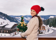 Woman with Christmas tree on balcony overlooking mountains Royalty Free Stock Photo