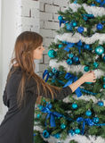 Woman at the Christmas tree decorated with blue balls Royalty Free Stock Photography