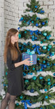 Woman at the Christmas tree decorated with blue balls Stock Photo