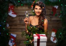 Woman in christmas tree dress. With glass of champagne and gift box Royalty Free Stock Image