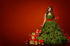 Woman Christmas Tree Dress with Present Gift, Xmas Fashion Gown. Over Red New Year Background Royalty Free Stock Photography