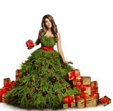 Woman Christmas Tree Dress and Presents Gifts, New Year Fashion. Woman Christmas Tree Dress and Presents Gifts, Fashion Model New Year Gown Isolated over White Royalty Free Stock Photo