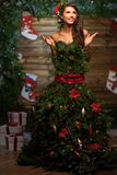 Woman in christmas tree dress. In wooden interior Stock Images
