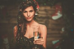 Woman in christmas tree dress. In wooden interior with glass of champagne Stock Photos