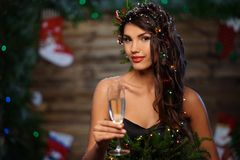 Woman in christmas tree dress. In wooden interior with glass of champagne Stock Images