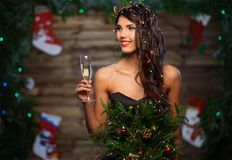 Woman in christmas tree dress. In wooden interior with glass of champagne Royalty Free Stock Photography