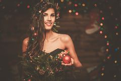 Woman in christmas tree dress. In wooden interior holding christmas toy Royalty Free Stock Image