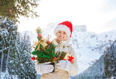 Woman with Christmas tree and gift box in the front of mountains Royalty Free Stock Photo
