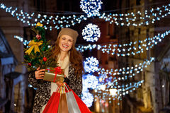 Woman with Christmas tree, gift and shopping bags in Venice. This Christmas is crushing on fashion forward shopping. Portrait of stylishly dressed smiling young stock photography