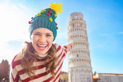 Woman in Christmas tree hat pointing on Leaning Tour of Pisa Royalty Free Stock Images