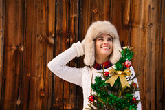 Woman with Christmas tree near rustic wall looking on copy space Stock Photos