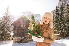 Woman with Christmas tree standing in front of mountain house Stock Photo