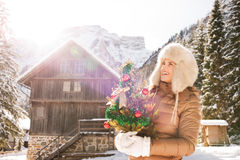 Woman with Christmas tree standing in front of mountain house Royalty Free Stock Images