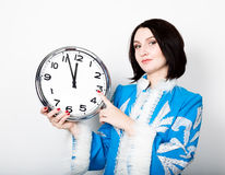 Woman in christmas uniform holding a clock, pointing at clockwise stock image