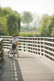 Woman ciclying on a bridge. Woman ciclying on a wooden bridge Royalty Free Stock Photo