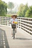 Woman ciclying on a bridge Stock Image