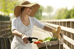 Woman cicyling with vegetables in her basket. Smiling woman cicyling with vegetables in her basket Royalty Free Stock Photo