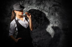 Woman with cigar on grey wall Royalty Free Stock Images
