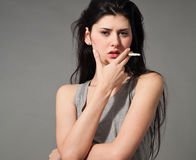 Woman with a cigarette. Fashion style photo of a beautiful young brunette woman holding a cigarette,studio shot Royalty Free Stock Photos