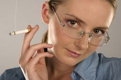 Woman with a cigarette. Young girl, woman in glasses with a cigarette Stock Photo