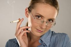 Woman with a cigarette. Young girl, woman in glasses with a cigarette Stock Photos