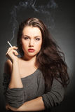 Woman with cigarette. Fashion portrait the woman with cigarette on a grey background Stock Photos